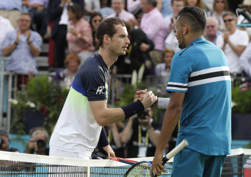 Andy Murray of Britain, left, shakes hands with Nick Kyrgios of Australia, right, after Kyrgios won their singles tennis match at the Queen's Club tennis tournament in London, Tuesday, June 19, 2018. (AP Photo/Kirsty Wigglesworth)
