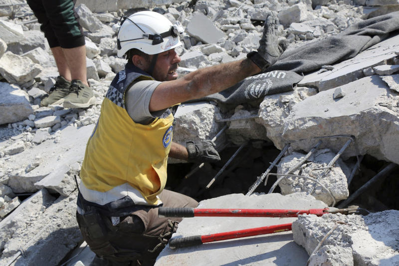 This photo provided by the Syrian Civil Defense White Helmets, which has been authenticated based on its contents and other AP reporting, shows a Civil Defense worker searching for victims from under the rubble of a destroyed building that hit by airstrikes, in Deir al-Sharqi village, in Idlib province, Syria, Saturday, Aug 17, 2019. Syrian activists and a war monitor say airstrikes have pounded the southern edge of a rebel stronghold in the country's northwest, in one instance killing seven including children. (Syrian Civil Defense White Helmets via AP)