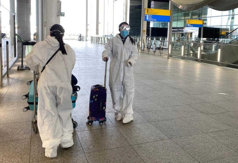 Passengers wearing protective clothing are seen at Heathrow Airport, London