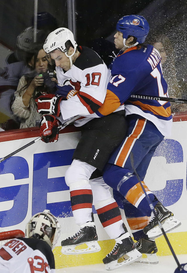 New Jersey Devils' Peter Harrold, left, is checked by New York Islanders left wing Matt Martin during the second period of a preseason NHL hockey game, Saturday, Sept. 21, 2013, in New York. (AP Photo/Julio Cortez)