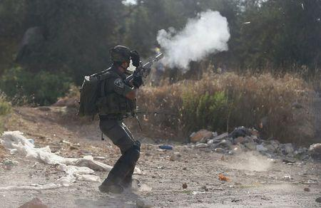 An Israeli border policeman fires a tear gas canister towards Palestinians during clashes following the funeral of Palestinian youth Laith al-Khaldi, in Jalazoun refugee camp near the West Bank city of Ramallah August 1, 2015. REUTERS/Mohamad Torokman