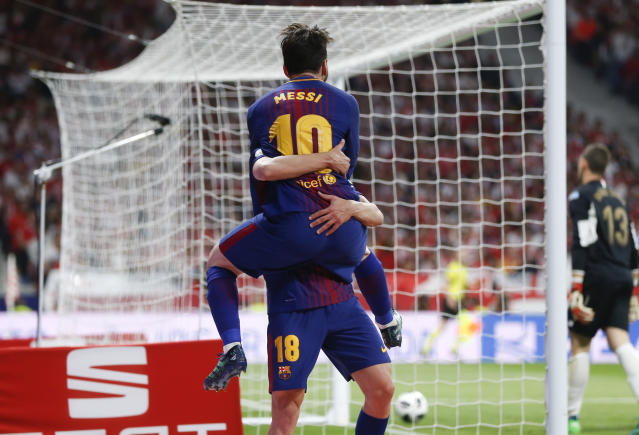 Barcelona's Lionel Messi celebrates with Barcelona's Jordi Alba after scoring second goal against Sevilla during the Copa del Rey final soccer match between Barcelona and Sevilla at the Wanda Metropolitano stadium in Madrid, Spain, Saturday, April 21, 2018. (AP Photo/Francisco Seco)
