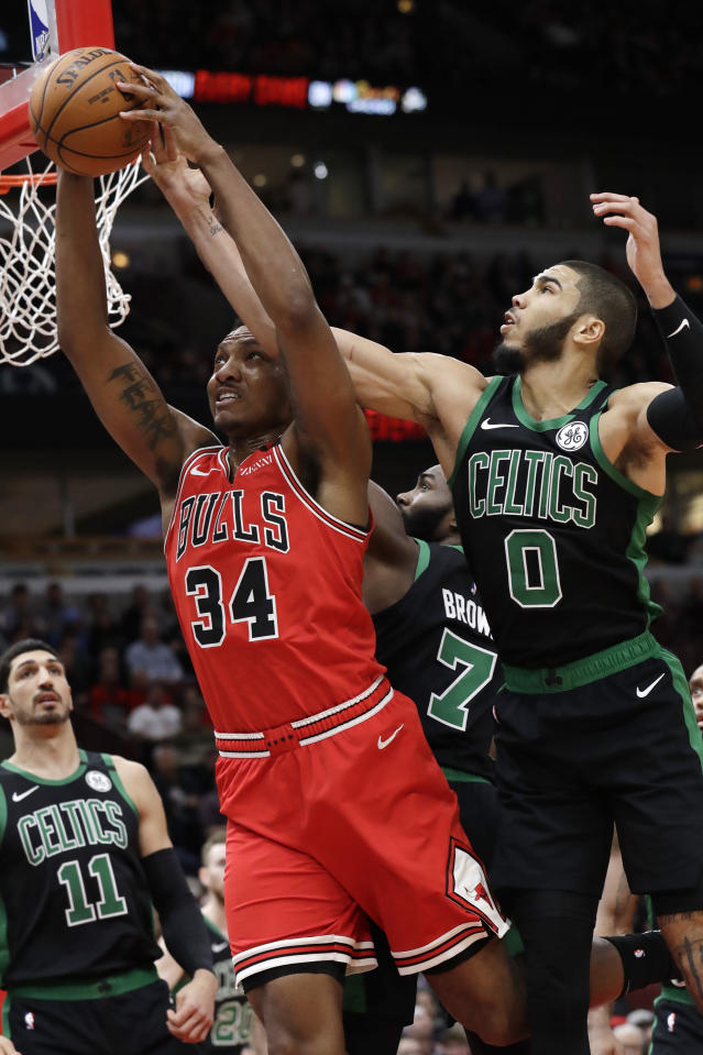 Chicago Bulls center Wendell Carter Jr., left, pulls in a rebound next to Boston Celtics forward Jayson Tatum (0) and guard Jaylen Brown (7) during the first half of an NBA basketball game in Chicago, Saturday, Jan. 4, 2020. (AP Photo/Nam Y. Huh)