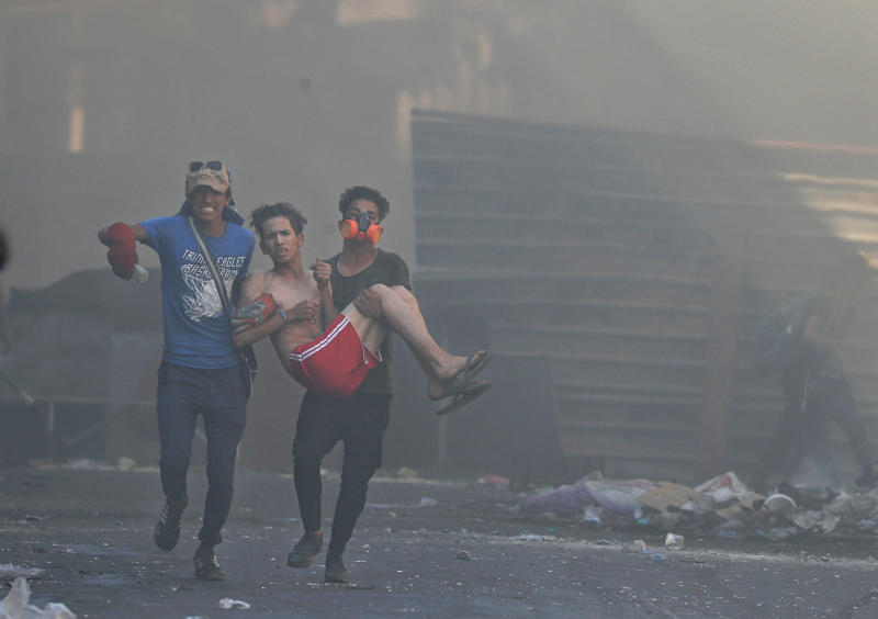 An injured protester is rushed to a hospital Iraqi riot police fire tear gas during clashes between Iraqi security forces and anti-government protesters in the al-Rasheed street in Baghdad, Iraq, Friday, Nov. 8, 2019.  The demonstrators complain of widespread corruption, lack of job opportunities and poor basic services, including regular power cuts despite Iraq's vast oil reserves. They have snubbed limited economic reforms proposed by the government, calling for it to resign. (AP Photo/Khalid Mohammed)