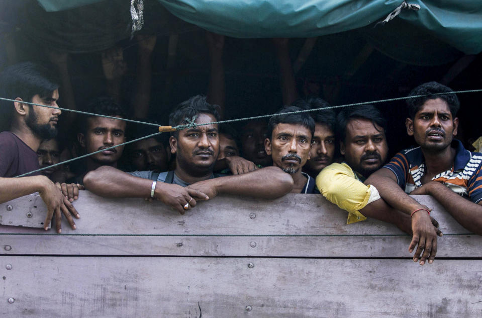 Men from Bangladesh ride in the back of a truck heading to an immigration detention center in Medan, North Sumatra, Indonesia, Wednesday, Feb. 6, 2019. Officials said a few dozen men were found locked in a house, waiting for a broker to bring them illegally by boat to Malaysia, with some planning to work on palm oil plantations. (AP Photo/Binsar Bakkara)