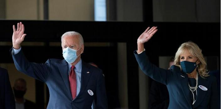 Democratic presidential candidate Joe Biden and his wife Jill Biden wave as they walk out of the Carvel Delaware State Building after voting in Wilmington on October 28, 2020 ahead of Election Day