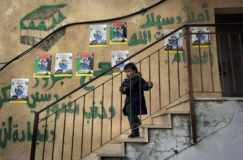 "A child walks down the stairs of the family home of Ahmed Shehadeh, one of 26 Palestinian prisoners expected to be released later tonight, next to posters with his picture and Arabic that reads ""welcome,"" in the Qalandia refugee camp at the outskirts of the West Bank city of Ramallah, Monday, Dec. 30, 2013. Israel and the Palestinians are gearing up for the expected release by Israel of 26 of the longest-serving Palestinian prisoners, who were all convicted in deadly attacks of Israelis, as part of a U.S.-brokered package to restart peace talks. (AP Photo/Nasser Nasser)"