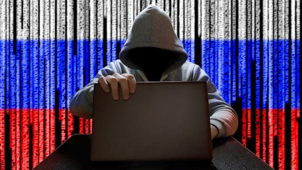 PHOTO: A hooded figure works on a laptop with a Russian Flag digital code backdrop in an undated stock image. (STOCK IMAGE Trambler58/Shutterstock )