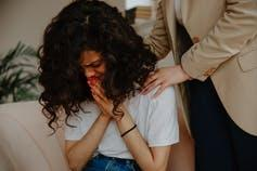 A woman is comforted as she cries.
