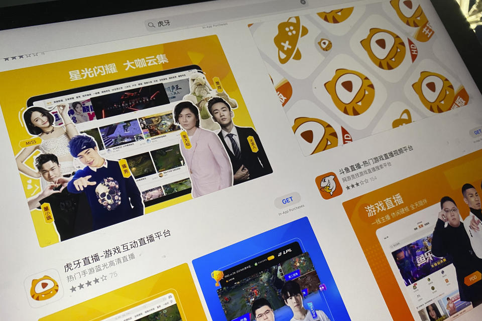 An app store page showing the apps Huya and Douyu is seen on a screen in Beijing on Saturday, July 10, 2021. China's market regulator on Saturday blocked the merger of Tencent-backed game streaming platforms Douyu and Huya following an anti-monopoly investigation, as authorities ramp up scrutiny of some of the country's biggest technology companies. (AP Photo/Ng Han Guan)