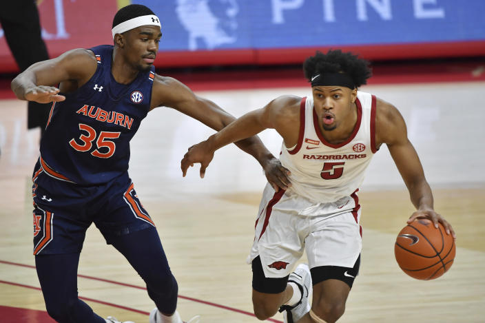 Arkansas guard Moses Moody (5) tries to get past Auburn defender Devan Cambridge (35) during the first half of an NCAA college basketball game Wednesday, Jan. 20, 2021, in Fayetteville, Ark. (AP Photo/Michael Woods)