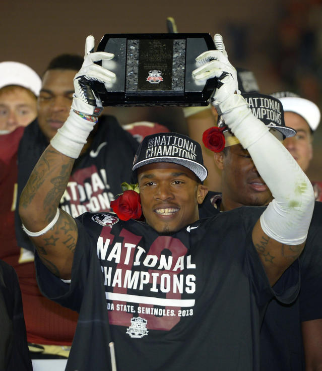 Florida State's P.J. Williams (26) holds up a trophy after the NCAA BCS National Championship college football game against Auburn Monday, Jan. 6, 2014, in Pasadena, Calif. Florida State won 34-31. (AP Photo/Mark J. Terrill)
