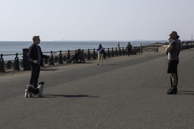 People engage in conversation while adhering social distancing rules in Brighton. (PA)