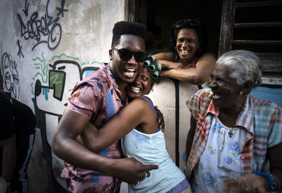 Cuban singer Cimafunk hugs a woman during a music conga through the streets of Cuba's Old Havana neighborhood during the 35th Havana International Jazz Festival on Jan. 15, 2020. (AP Photo/Ramon Espinosa)
