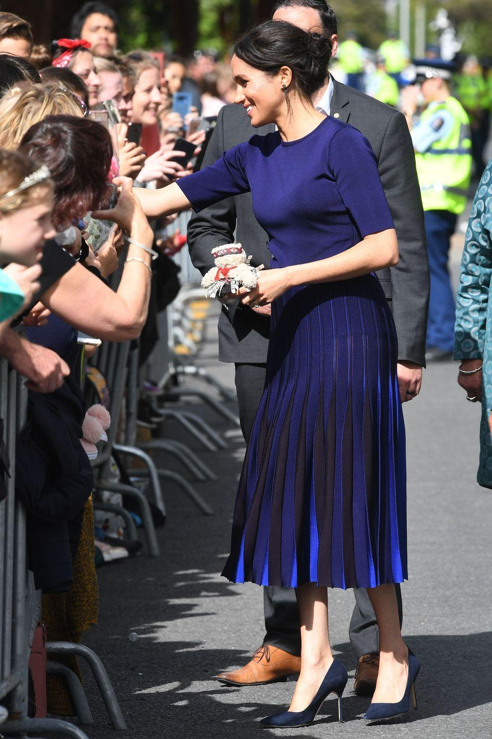 "<p>For one of her final outfits of the royal tour, Meghan stepped out in a custom navy Givenchy look. The Duchess also wore a pair of pumps by Manolo Blahnik.</p><p><a class=""link rapid-noclick-resp"" href=""https://www.barneys.com/product/manolo-blahnik-bb-pumps-503345489.html"" rel=""nofollow noopener"" target=""_blank"" data-ylk=""slk:SHOP NOW"">SHOP NOW</a> <em>Manolo Blahnik Pumps, $625</em></p>"