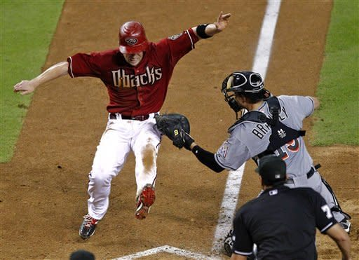 Miami Marlins catcher Rob Brantly tags out Arizona Diamondbacks' Aaron Hill at the plate during the eighth inning of a baseball game, the second game of a doubleheader, Wednesday, Aug. 22, 2012, in Phoenix. (AP Photo/Matt York)