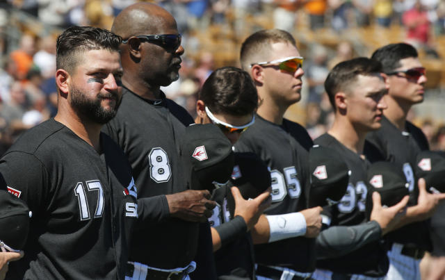 Chicago White Sox first baseman Yonder Alonso (17), first base coach Daryl Boston (8) and other team members stand for the national anthem before a spring training baseball game against the San Francisco Giants, Monday, March 18, 2019, in Glendale, Ariz. (AP Photo/Sue Ogrocki)