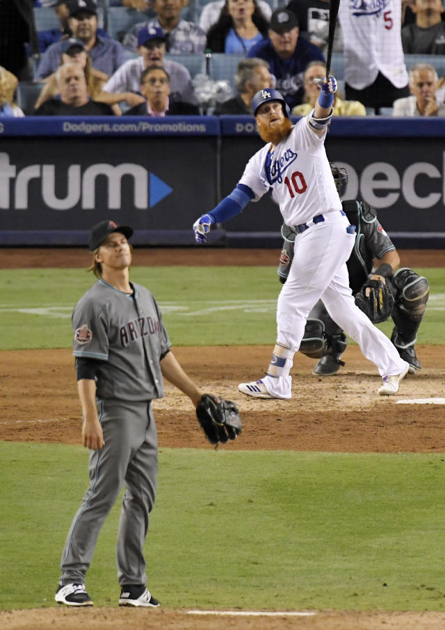 Los Angeles Dodgers' Justin Turner watches his solo home run off Arizona Diamondbacks starting pitcher Zack Greinke, left, during the eighth inning of a baseball game Friday, Aug. 31, 2018, in Los Angeles. (AP Photo/Mark J. Terrill)