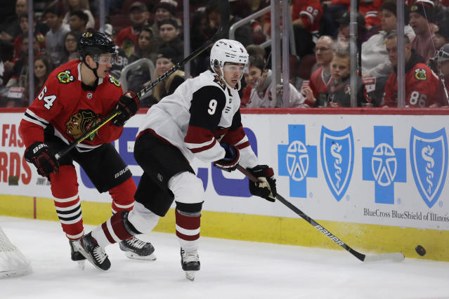Arizona Coyotes right wing Clayton Keller, right, looks to pass against Chicago Blackhawks center David Kampf during the first period of an NHL hockey game Sunday, Dec. 8, 2019, in Chicago. (AP Photo/Nam Y. Huh)