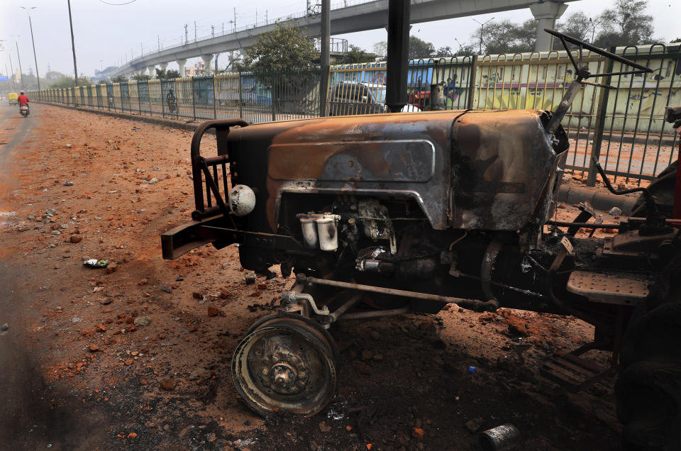 A burnt tractor stands on a road littered with stones after Tuesday's violence in New Delhi, India, Wednesday, Feb. 26, 2020. At least 20 people were killed in three days of clashes in New Delhi, with the death toll expected to rise as hospitals were overflowed with dozens of injured people, authorities said Wednesday. The clashes between Hindu mobs and Muslims protesting a contentious new citizenship law that fast-tracks naturalization for foreign-born religious minorities of all major faiths in South Asia except Islam escalated Tuesday. (AP Photo/Manish Swarup)