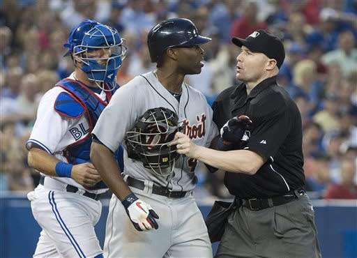 Home plate umpire Mike Estabrook, right, holds back Detroit Tigers' Torii Hunter, center, next to Toronto Blue Jays catcher J.P. Arencibia, left, as Hunter stares at Toronto Blue Jays pitcher Todd Redmond after being hit by a pitch during the sixth inning of a baseball game Wednesday, July 3, 2013, in Toronto. The Tigers won 6-2. (AP Photo/The Canadian Press, Nathan Denette)