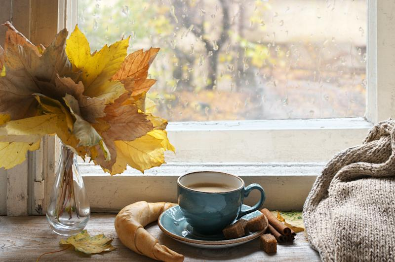 Cozy autumn still life: cup of coffee with croissant and cinnamon, bouquet of fall leaves and warm sweater on vintage wooden windowsill against rainy weather from outside.
