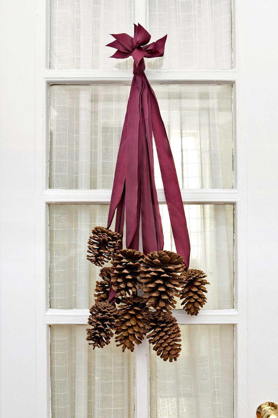<p>Not all DIY front-door decor requires a foam wreath form. To make this elegant cluster, we selected 8 four- to six-inch pinecones and 8 two-foot-long pieces of silk ribbon. Use a hot-glue gun to adhere the last two inches of each ribbon to the base of a cone. After the glue dries, collect all the ribbon ends and stagger them so that the cones fall at varying lengths. Tie the ribbon ends together in a knot, trim the tips so they are uniform, and slip the knot over a finishing nail.</p>