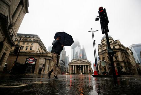 People walk through the financial district during rainy weather in London