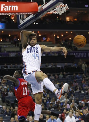Charlotte Bobcats' Jeffery Taylor (44) dunks over Philadelphia 76ers' Jrue Holiday (11) during the first half of an NBA basketball game in Charlotte, N.C., Friday, Nov. 30, 2012. (AP Photo/Chuck Burton)