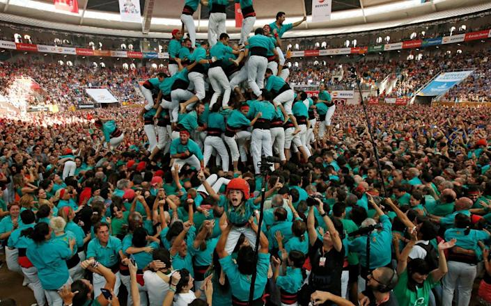 """<p>Castellers de Vilafranca celebrate after forming a human tower called """"castell"""" during a biannual competition in Tarragona city, Spain, Oct. 2, 2016. (REUTERS/Albert Gea)</p>"""