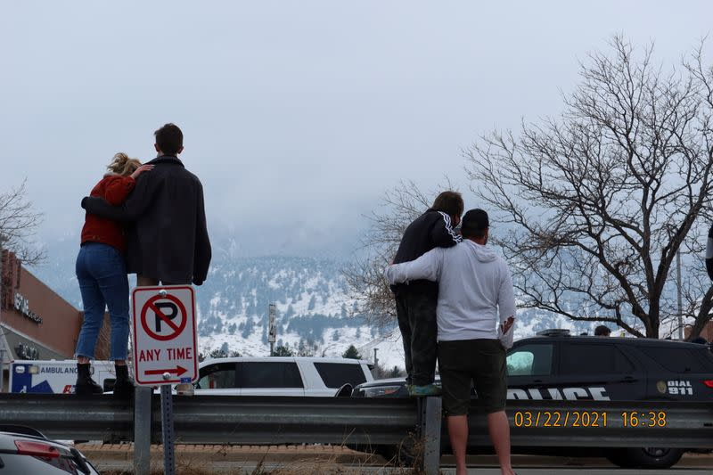 People stand near the scene where an active shooter was reported at a grocery store in Boulder