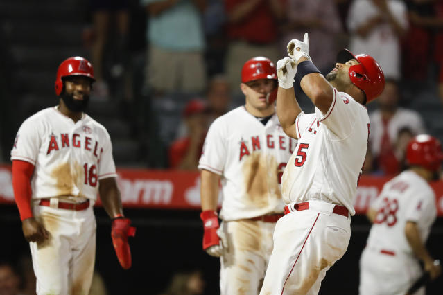 Los Angeles Angels' Albert Pujols, right, celebrates his three-run home run as Brian Goodwin, left, and Mike Trout watch, during the eighth inning against the Boston Red Sox in a baseball game in Anaheim, Calif., Saturday, Aug. 31, 2019. (AP Photo/Chris Carlson)