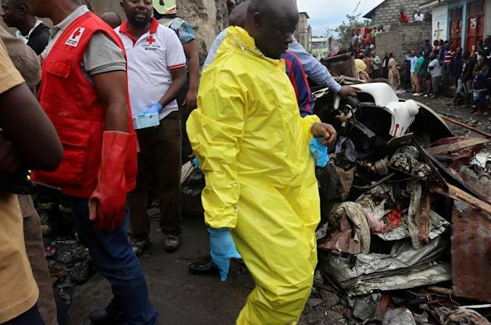 Civilians gather at the site where a Dornier 228-200 plane operated by local company Busy Bee crashed into a densely populated neighborhood in Goma