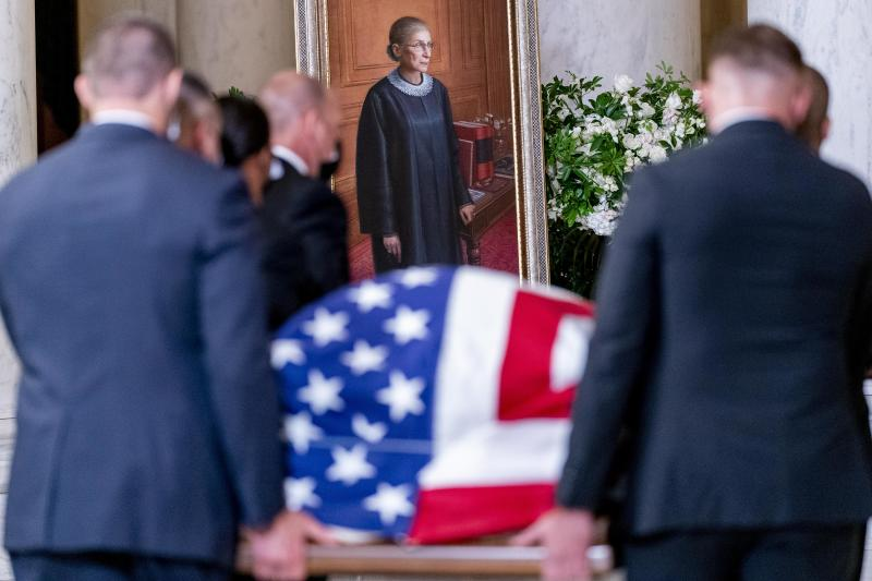 The flag-draped casket of Associate Justice Ruth Bader Ginsburg, carried by Supreme Court police officers, arrives in the Great Hall at the Supreme Court on Wednesday. (Andrew Harnik-Pool/Getty Images)