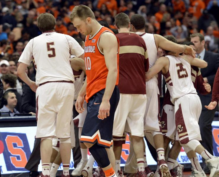 Syracuse's Trecor Cooney walks off the court as Boston College players celebrate after Boston College defeated Syracuse 62-59 in overtime in an NCAA college basketball game in Syracuse, N.Y., Wednesday, Feb. 19, 2014. (AP Photo/Kevin Rivoli)