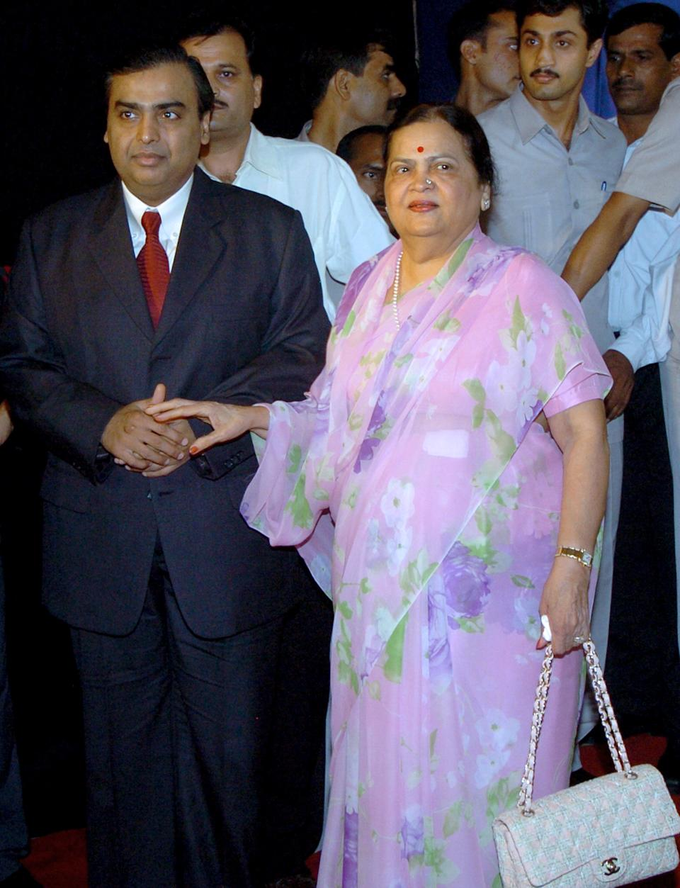 "(FILES) In this picture taken August 3, 2005, Chairman of Reliance Industries Limited Mukesh Ambani (L) is accompanied by his mother Kokilaben as he arrives at the company's 31st Annual General Meeting in Mumbai. An Indian judge has told India's Ambani brothers to get their mother to settle their latest fight over natural gas supplies, telling them it is in the ""national interest,"" a report said on August 22, 2008. The two brothers, listed by Forbes magazine as among the world's six richest men, have been at odds since 2005 over a supply agreement from the Krishna Godavari basin off India's east coast. AFP PHOTO/Indranil MUKHERJEE/FILES"