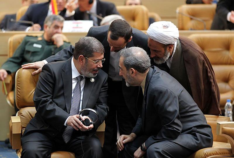 """In this photo released by the official website of the Iranian presidency office, Egyptian President Mohammed Morsi, left, talks with Iranian officials during opening session of Nonaligned Movement, NAM, summit, in Tehran, Iran, Thursday, Aug. 30, 2012. Morsi described the Syrian regime as """"oppressive"""" and called for it to transfer power to a democratic system during a visit to Syria's key regional ally Iran on Thursday. Ali Akbar Velayati, advisor to the Iranian supreme leader sits at right. AP Photo/Presidency Office)"""