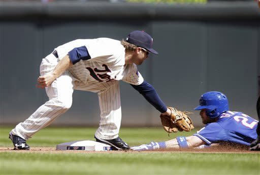 Minnesota Twins second baseman Brian Dozier, left, tags out Texas Rangers' Craig Gentry at second on a steal-attempt in the first inning of a baseball game on Saturday, April 27, 2013, in Minneapolis. (AP Photo/Jim Mone)