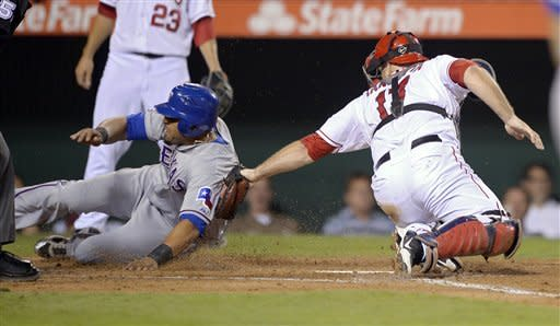 Texas Rangers' Nelson Cruz, left, scores ahead of the tagbyf Los Angeles Angels catcher Chris Iannetta on a sacrifice fly by Geovany Soto during the fifth inning of a baseball game, Thursday, Sept. 20, 2012, in Anaheim, Calif. (AP Photo/Mark J. Terrill)