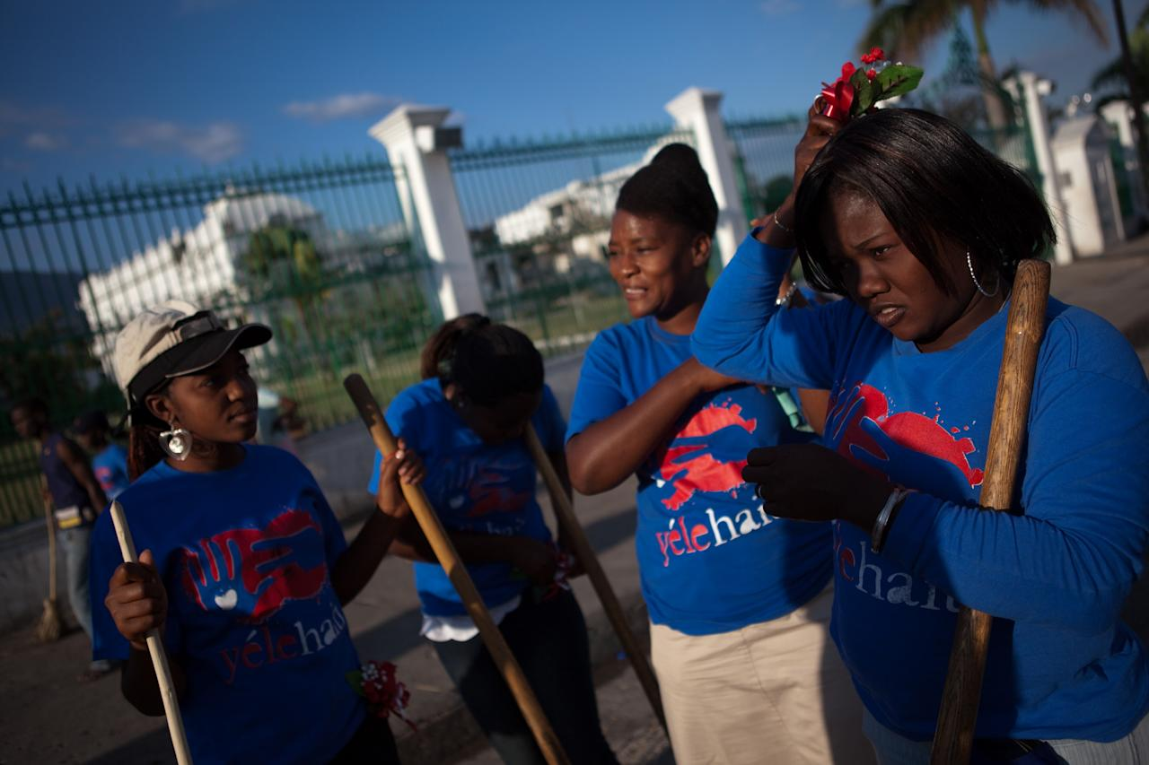 PORT-AU-PRINCE, HAITI - MARCH 8:  Women hired as part of a cash-for-work program by Yele Haiti, an NGO operated by entertainer Wyclef Jean, pause to attach corsages of plastic flowers-- a gift from a co-worker-- to their hair as they clean the streets in front of the Haitian national palace the morning after a carnival parade, March 8, 2011 in Port-au-Prince, Haiti.  The city has started dumping trash in an open area near the waterfront and along a main throroughfare. (Photo by Allison Shelley/Getty Images)