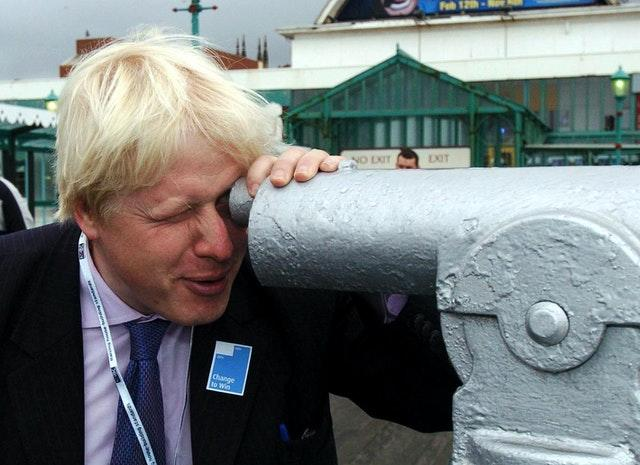 Boris Johnson looks through a telescope on the North Pier at Blackpool (Archive/PA)