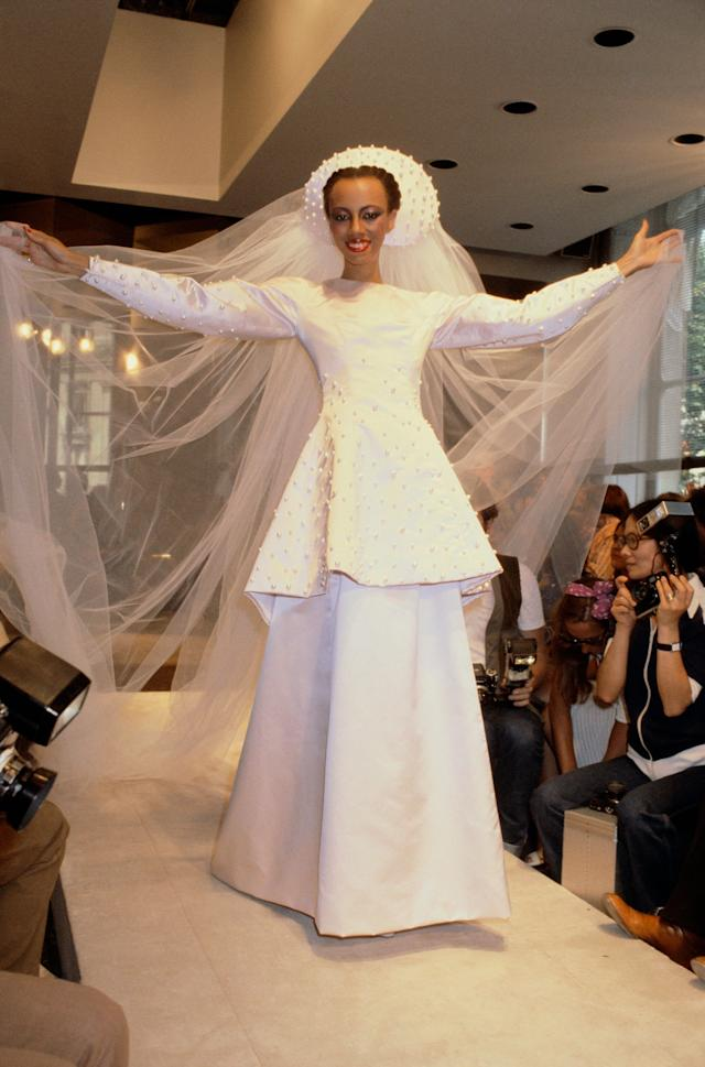 A model is wearing a wedding dress paired with a hat with a long tulle train during the Givenchy fall/winter 1979-1980 couture show in Paris.