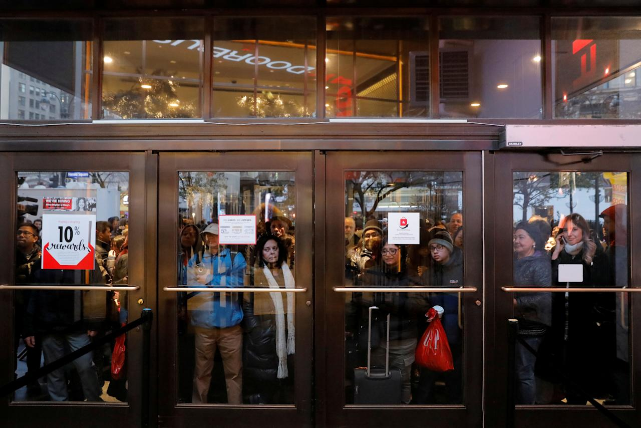 People gather at the Broadway entrance of Macy's Herald Square store ahead of early opening for the Black Friday sales in Manhattan, New York, U.S. November 23, 2017.  REUTERS/Andrew Kelly     TPX IMAGES OF THE DAY