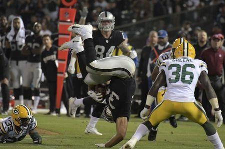 Aug 24, 2018; Oakland, CA, USA; Oakland Raiders running back Chris Warren (34) is upended as Green Bay Packers defensive back Raven Greene (36) watches during a preseason game at Oakland-Alameda County Coliseum. Mandatory Credit: Kirby Lee-USA TODAY Sports