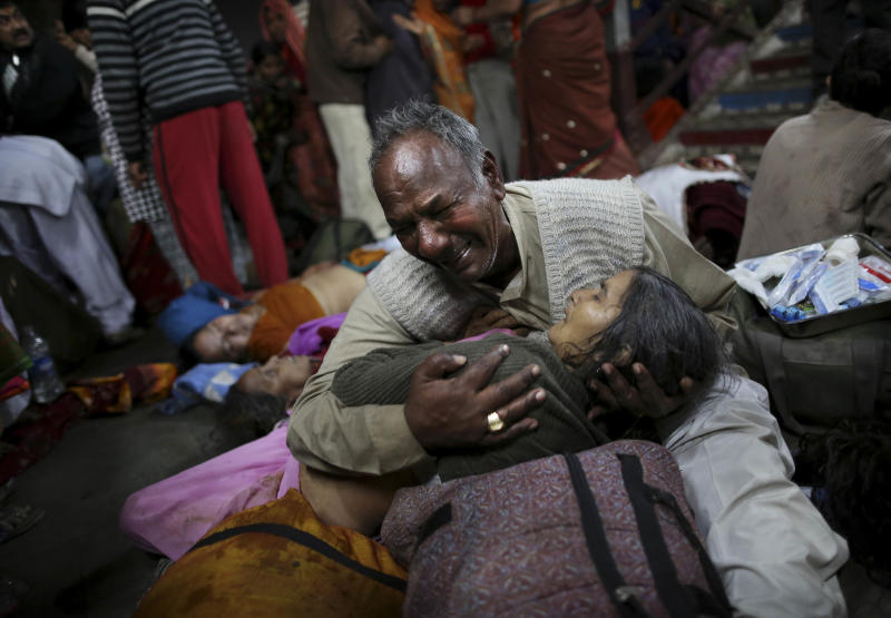 An Indian man weeps as he holds his wife who was killed in a stampede on a railway platform at the main railway station in Allahabad, India, Sunday, Feb. 10, 2013. At least ten Hindu pilgrims attending the Kumbh Mela were killed and more then thirty were injured in a stampede on an overcrowded staircase, according to Railway Ministry sources. (AP Photo/Kevin Frayer)