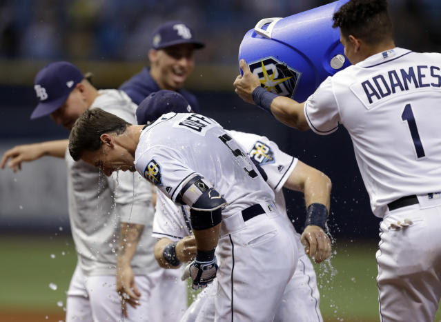 Tampa Bay Rays' Matt Duffy (5) gets doused with water by Willy Adames (1) after hitting the game-winning RBI single off Toronto Blue Jays relief pitcher Ryan Tepera in the ninth inning of a baseball game Wednesday, June 13, 2018, in St. Petersburg, Fla. The Rays won the game 1-0. (AP Photo/Chris O'Meara)