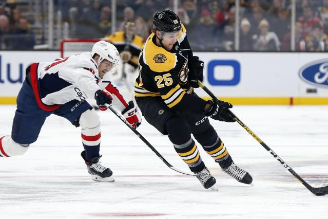 Boston Bruins' Brandon Carlo (25) brings the puck up against Washington Capitals' Lars Eller (20) during the first period of an NHL hockey game in Boston, Saturday, Nov. 16, 2019. (AP Photo/Michael Dwyer)
