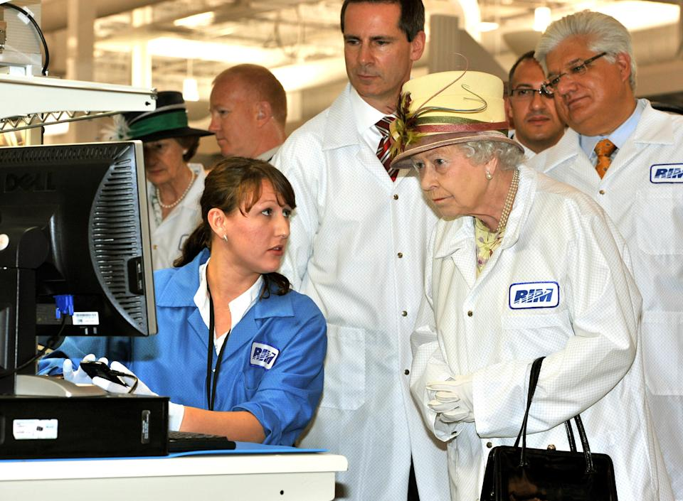 WATERLOO, ON - JULY 05:  Queen Elizabeth II, wearing a white protective coat (R), is shown a new product at the final testing before packaging test area during her tour of the RIM (Research In Motion) factory that produces the Blackberry mobile communications handset, on July 5, 2010 in Waterloo, Canada.  (Photo by John Stillwell - Pool/Getty Images)