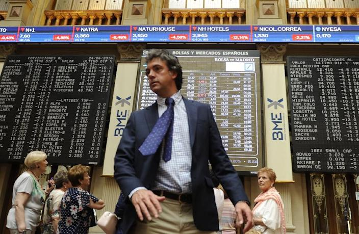 People stand Madrid stock exchange boards in Madrid on June 24, 2016 (AFP Photo/Curto De La Torre)