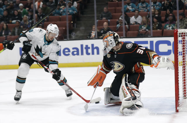 Anaheim Ducks goaltender John Gibson, right, stops a shot from San Jose Sharks' Tomas Hertl, left, during the first period of an NHL hockey game Friday, March 22, 2019, in Anaheim, Calif. (AP Photo/Marcio Jose Sanchez)